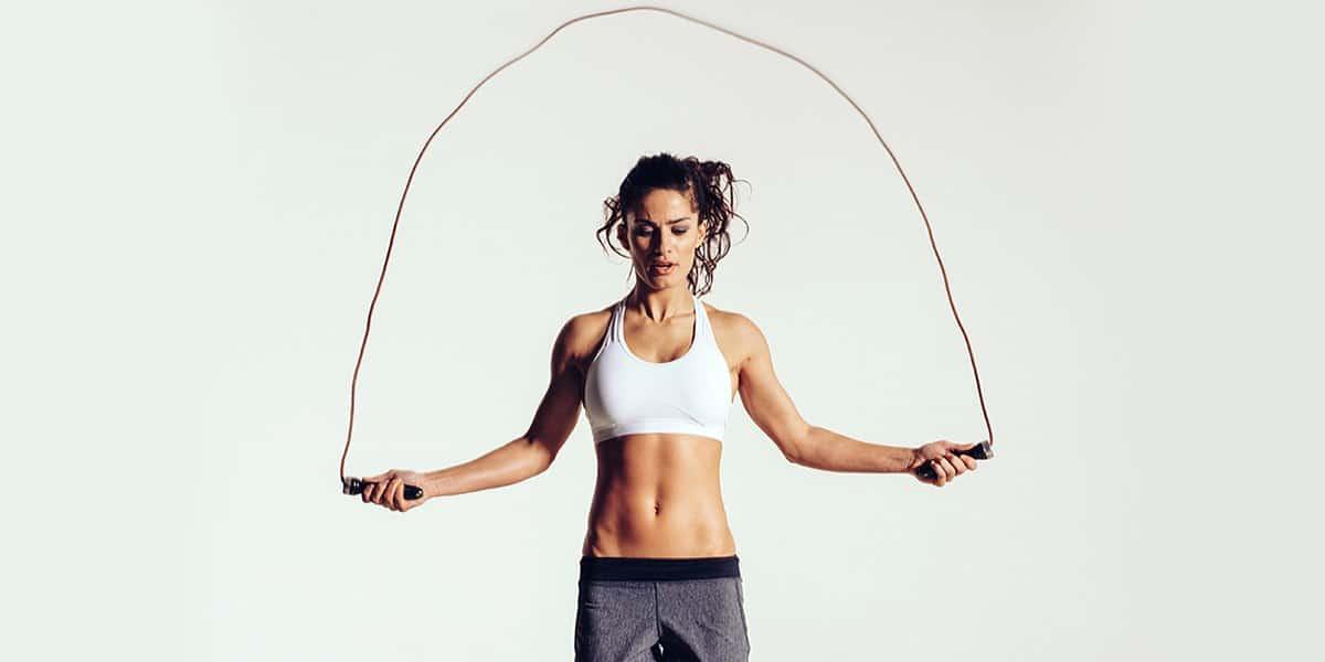 Beautiful and dedicated woman jumping rope.