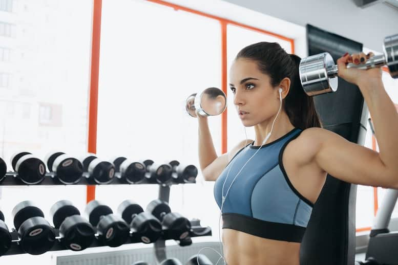 woman-listening-music-while-lifting-dumbells.